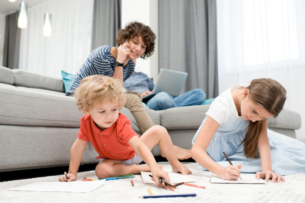 Mother making a phone call while watching her children draw.