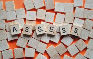 """Scrabble tiles spelling """"ASSESS""""."""
