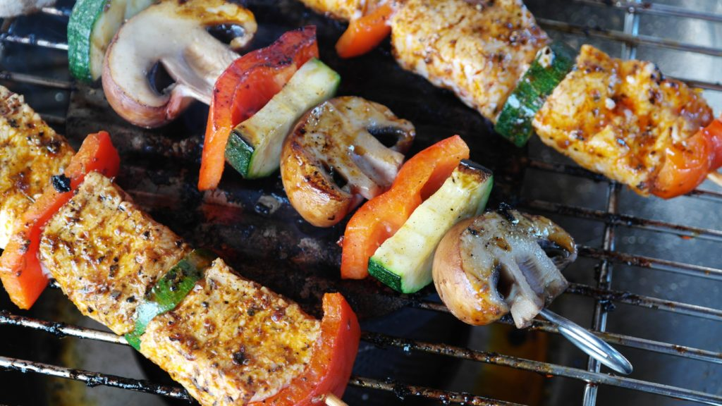 Skewers with mushrooms, zucchinis, bell peppers, and meat being grilled.