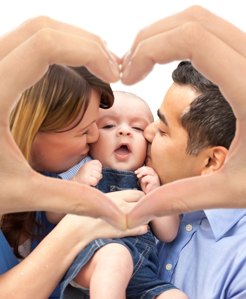 Parents kissing their baby, framed by hands making a heart shape.